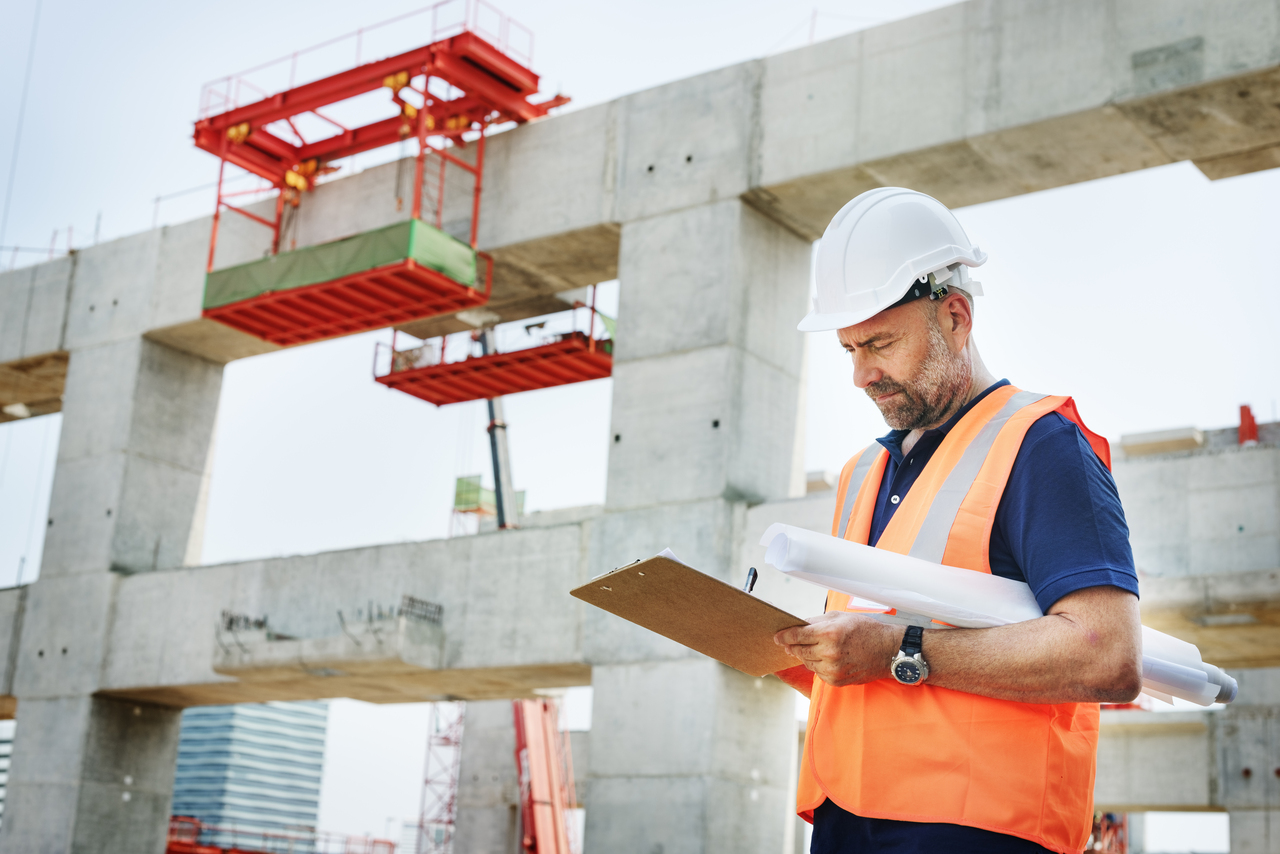 Construction site engineer looking at blueprint